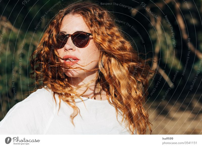 young woman with sunglasses and red curly hair turns towards the sun red hair red lips Curl Red-haired Woman already portrait Face Lips Lady Easygoing