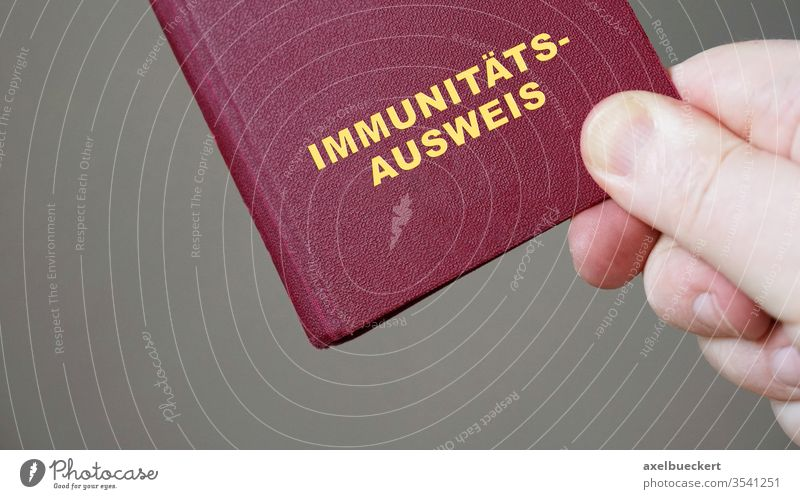 german immunity pass or passport - hand holding mock-up european immune certificate travel document corona coronavirus covid-19 germany immunization pandemic