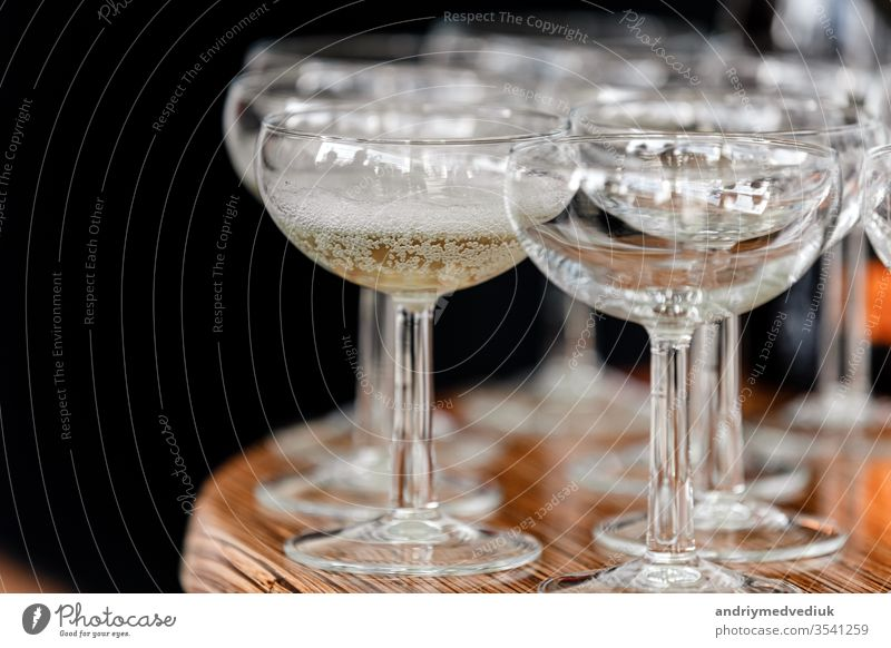 sparkling wine, champagne in glasses on the wooden table on black background in the restaurant. selective focus hand waitress catering group gloves open party