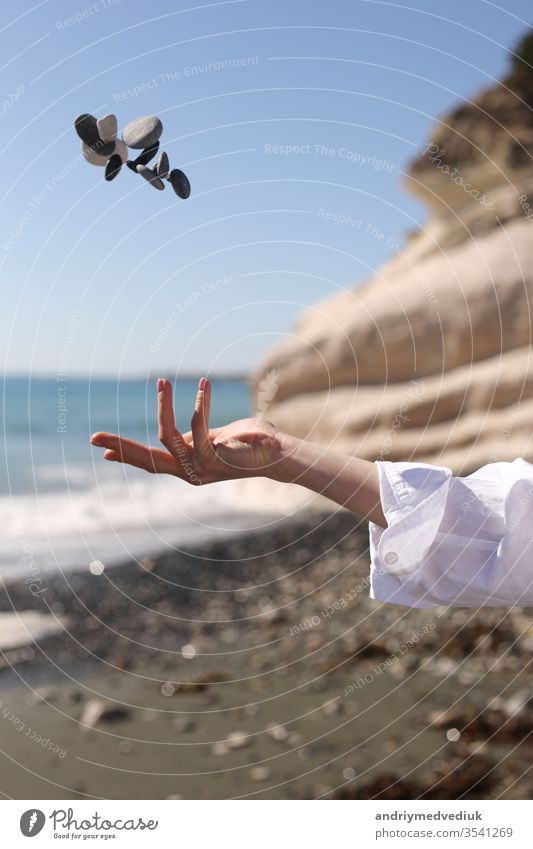 female hand throws a pebble in her hand against the background of the blue sky, beach, rock and sea. girl young nature summer beauty travel people lifestyle
