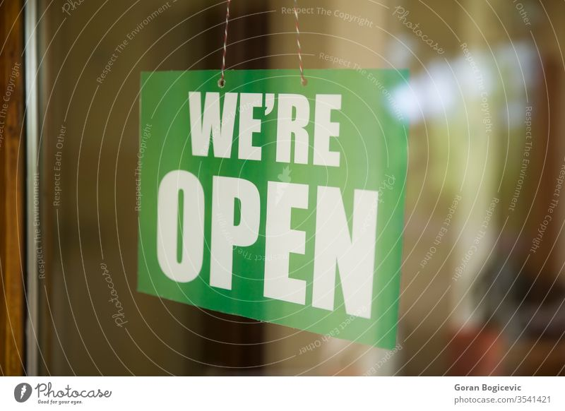 Open sign on the glass of the door at store advertising banner bar board business busy cafe city concept day entrance exterior front hanging hours information