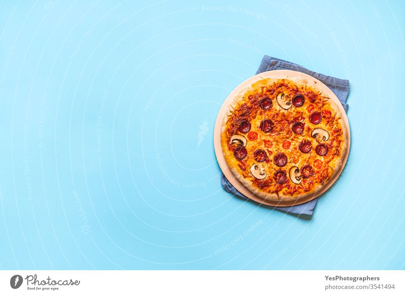 Pizza pepperoni hot from the oven. Homemade pizza Italian above view artisan authentic baked blue background cheese convenience food cooked copy space cuisine