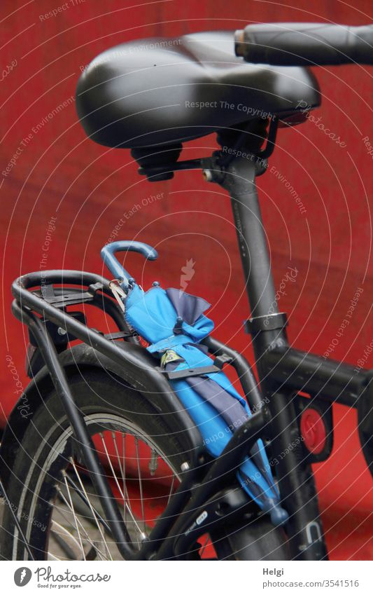 there could be rain - detail view of a black bicycle with a blue umbrella, which is stuck on the luggage rack Bicycle Transport Netherlands Cycling