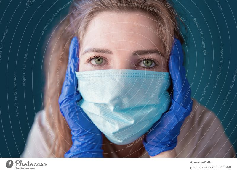 Young woman wearing protective gloves and face mask inside a home in quarantine looking bored and sad, for Covid-19 Coronavirus, with blue background medical