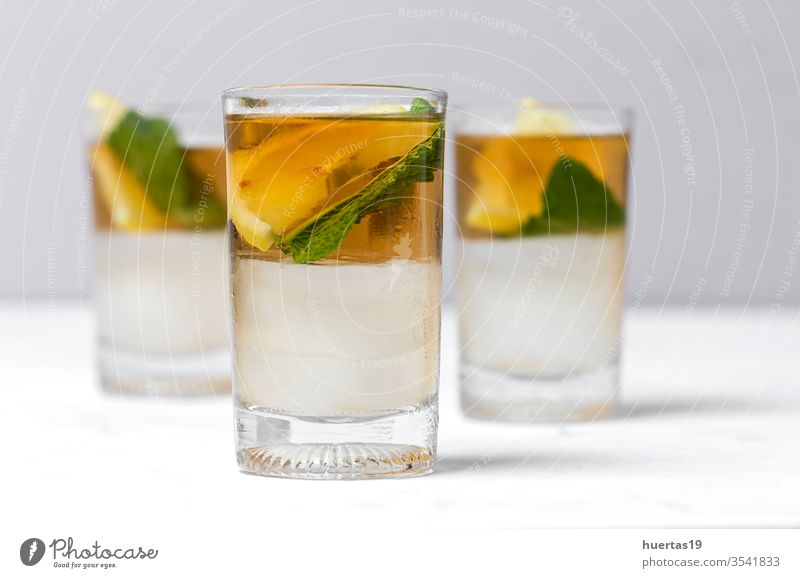tea with ice, mint and lemon wedges on white table cold drink iced glass refreshment sweet cube cool liquid background beverage summer food healthy green