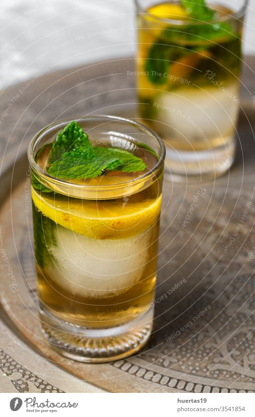 Refreshing glasses of tea with ice, mint and lemon wedges cold drink iced refreshment sweet cube cool liquid background beverage summer food healthy green