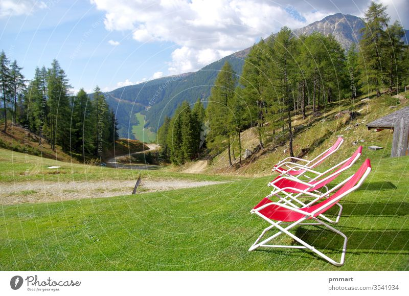 red deckchairs to rest hikers and admire the high mountains with meadows, woods and rocks benches sitting stone live beautiful light sun green tops sky clear
