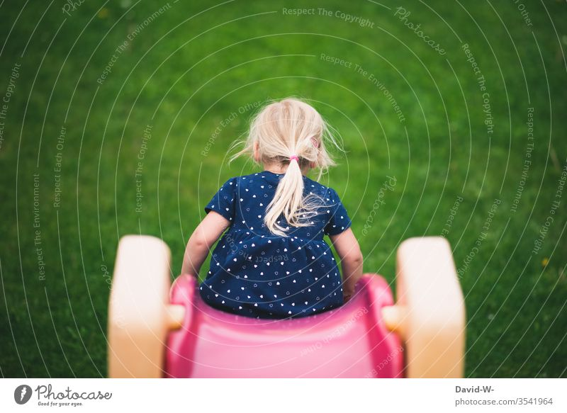 Child slides down the slide girl Skid Slide Garden Playing out Nature Rear view Infancy Leisure and hobbies Joy Colour photo Day Toddler