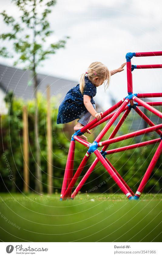 Girl climbing on a climbing frame in the garden girl climbs Climbing fun Joy courageous children Childlike Cute Playing Employment Garden toys Effortless