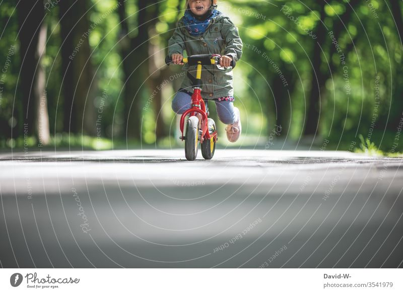 Child rides his bike outside through nature Infancy Joy Bicycle Cycling Small Toddler girl Cute swift children smile Mouth Handlebars To hold on Park Street