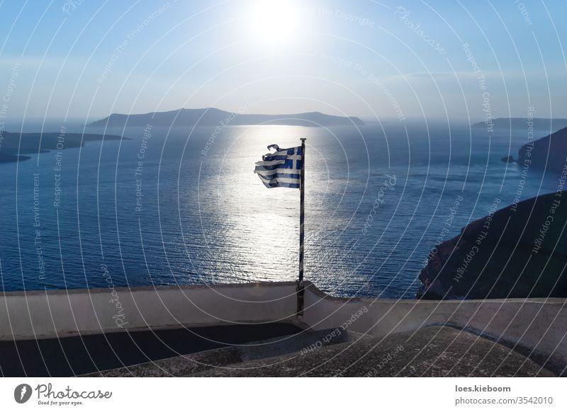 Greek torn flag on backlight of the shining ocean of last sun, Santorini, Greece greece greek sunset broken santorini island sea summer aegean travel cyclades