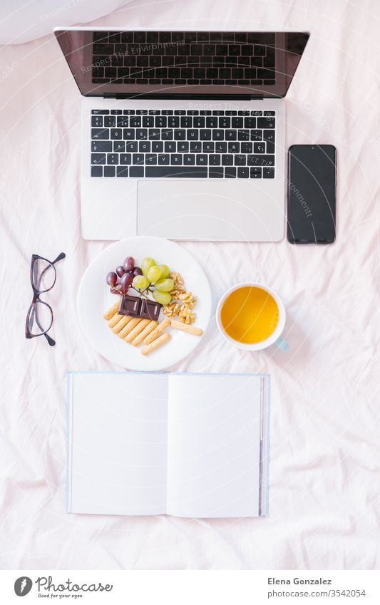 Flat lay. Tea at home in her bed, checking her laptop, reading a book and having breakfast. Top view flat lay books snack cozy indoors comfort comfortable