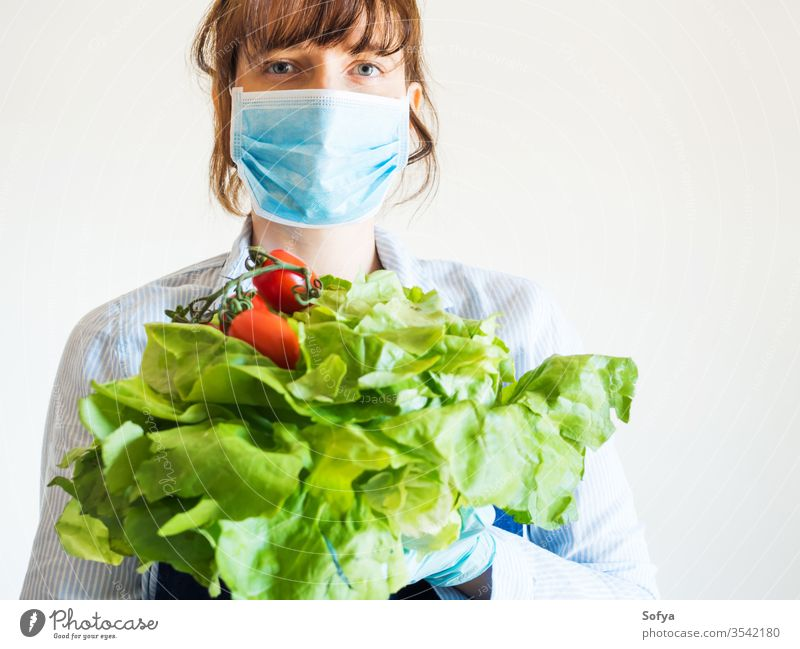 Woman in blue in face mask with fresh produce food delivery grocery store farm shop owner necessities hands safe staples girl foodstuff gloves holding online