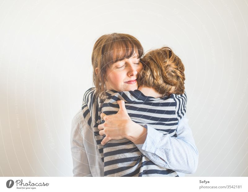 Young mother and child hugging. Mothers day mom parent mothers day woman lifestyle kid love son together family emotion feelings face eyes caucasian happy