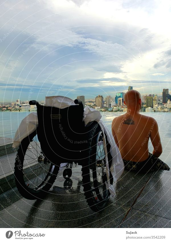 Wheelchair users enjoy the evening atmosphere at the Infinity Pool above the rooftops of Bangkok wheelchair users Handicapped Human being Exterior shot Mobility