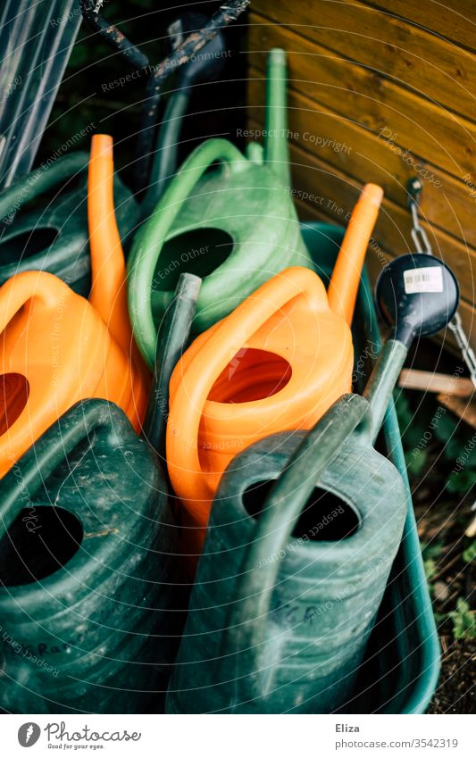 Different coloured watering cans variegated green Orange Gardening Watering can Gardener Devices Cast Empty Day