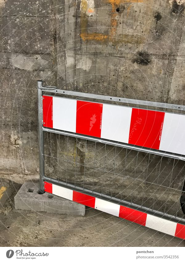 A red-white striped barrier leans against a concrete wall cordon Control barrier Warn interdiction Stripe Reddish white Wall (building) Grating Dirty