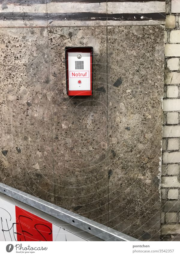 Emergency call system with red button mounted on a house facade. Danger, security, threat . Red knob Alarm Appliance Wall (building) Control barrier Striped