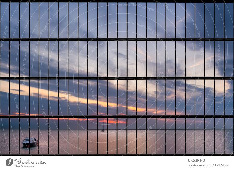 wanderlust but no freedom   the beautiful sunset at the sea hides behind bars Sunset Grating Ocean Horizon closed nature no passage Clouds calm sea Sky Water