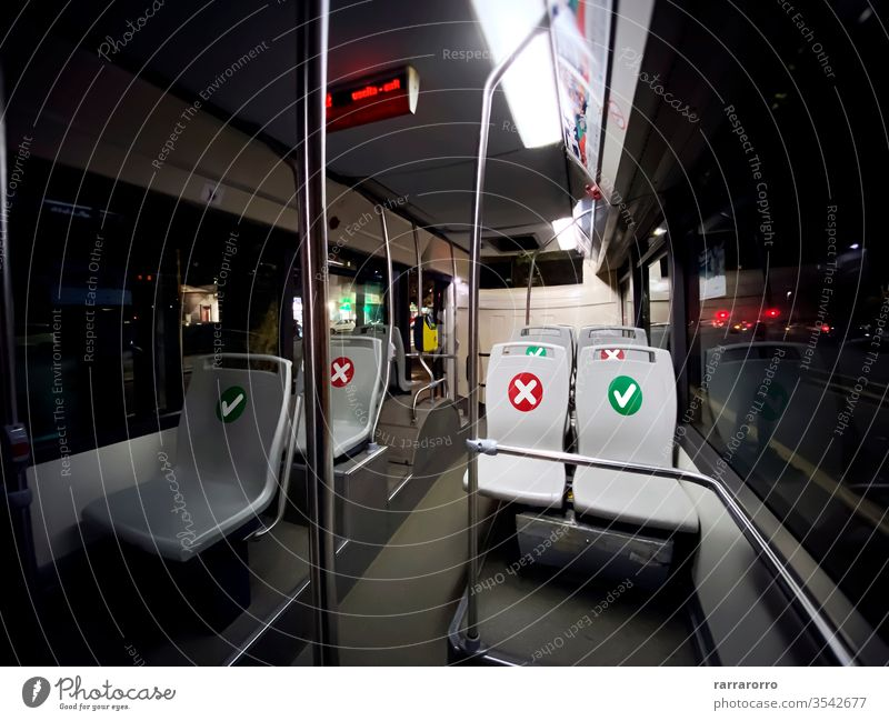 interior of a public transport bus with empty seats with the indication of where is possible to sit social distancing coronavirus covid-19 safety transportation