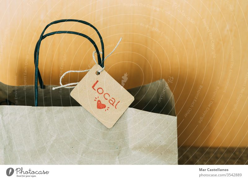 Paper shopping bag at the front door of the house. Concept of shopping. paper label entrance mat recyclable sales local trade cardboard reusable copy space