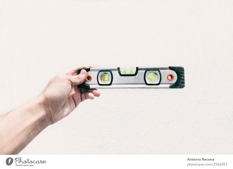 A hand holds a level in front of a white wall isolated construction handyman tool work job leveling spirit bubble spirit level body parts worker object
