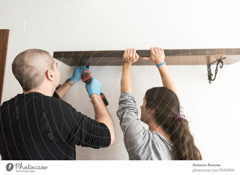 man with electric screwdriver places bookshelf on a wall with the help of his wife's handyman bald beard beginnings casual caucasian change construction