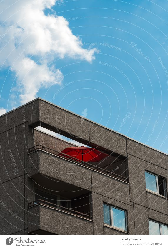 The red parasol on the balcony on the apartment block architecture balconies Berlin blue building building exterior cement city clean cloud clouds concept day