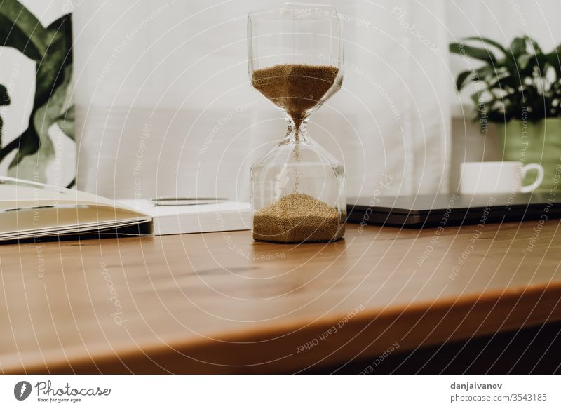 hourglass on a wooden table time sand clock timer isolated white sandglass antique countdown object watch old sand-glass minute past instrument retro deadline