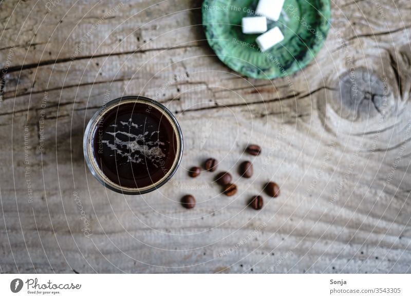Coffee in a glass and sugar cubes on a green plate. Rustic wooden table, top view. Beverage Espresso glass cup Strong Aromatic Caffeine breakfast Wooden table