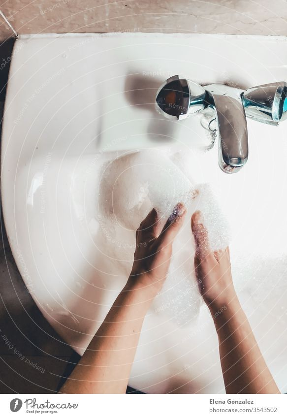 Woman washing her hands in bathroom to prevent Covid-19 infection. Recommended washing with soap and running water during coronavirus pandemic. Top view women
