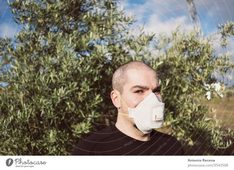 Man with sanitary mask with possible olive allergy or fear of coronavirus surgery healthy man pollution pollen covid 19 corona virus caution male adult person
