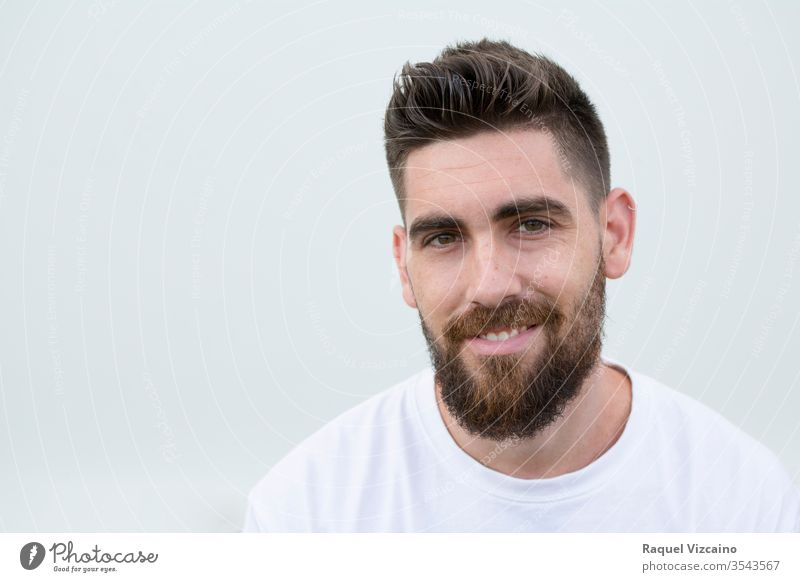 Portrait of a very handsome, Caucasian, smiling, and happy man with a beard and white shirt. portrait face isolated young people guy person expression smile