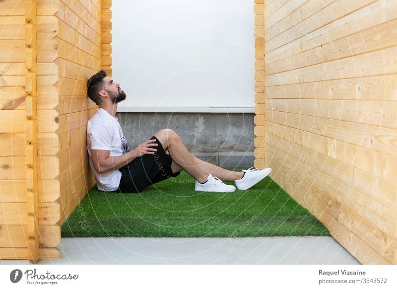 A handsome man sitting on the artificial grass between two wooden cabins. seated white health relaxation wellness house home zen outdoors relaxing loneliness