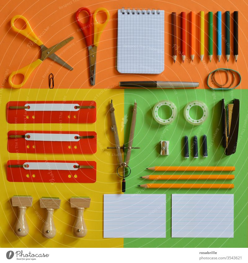 colourful flat lay with office utensils such as scissors stamps compasses ink cartridge fountain pen rubber band coloured pencils pencils quick fasteners paper clip notepad stapler tacker adhesive tape index cards on orange yellow green paper against the dreary everyday working life