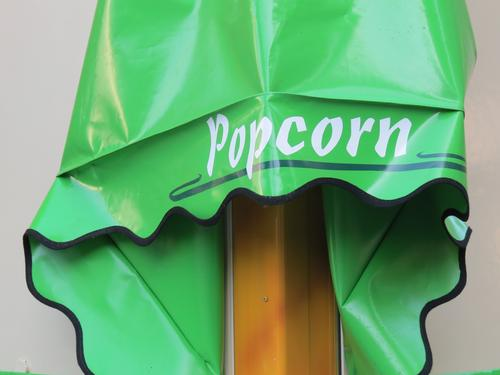 Advertising for popcorn on green lacquer foil Characters Letters (alphabet) Word Typography Signs and labeling Signage Exterior shot Colour photo White