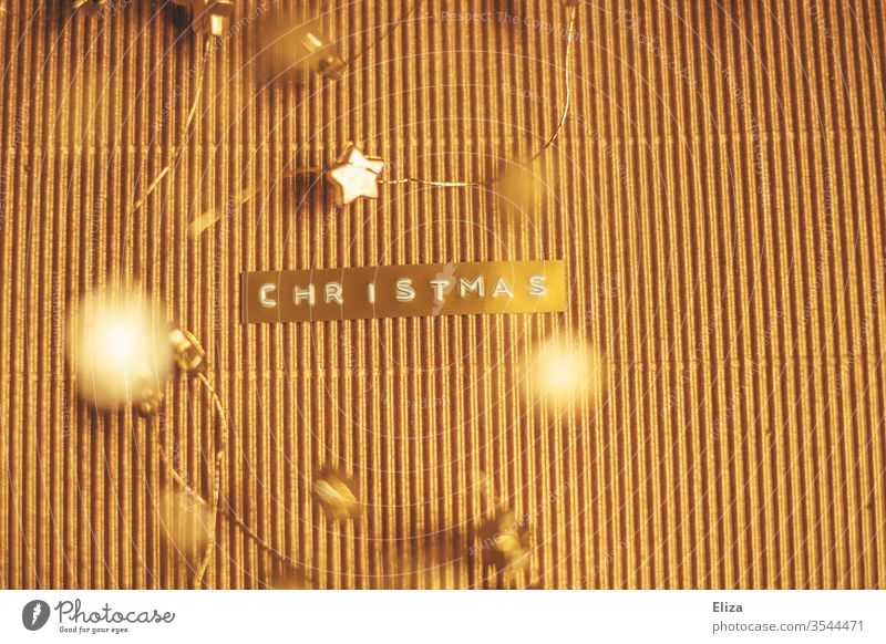 The word Christmas embossed on a gold label on a shimmering gold background with gold stars around it. Word Text merry christmas golden Label Christmas & Advent
