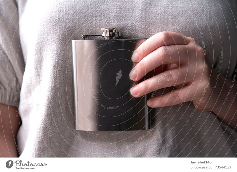 Hand holding a stainless steel flask for liqueur, alcohol and beverage concepts in close-up background alcoholic Drinking Design by hand booze Party Steel Water