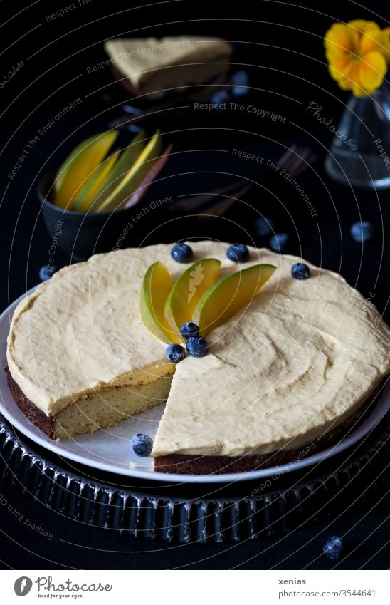 Sweet, round cake with white chocolate and mango cream, decorated with blueberries and mango slices, cake piece and vase in dark background Cake Mango