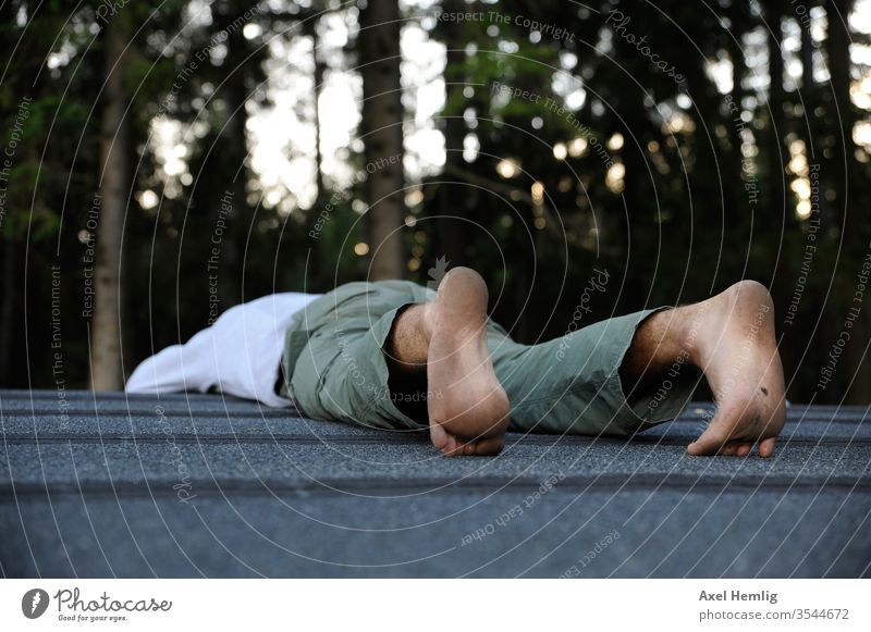 Man lies face down on a roof tranquillity Calm Be quiet! Exterior shot Relaxation Serene To be silent Loneliness calm Day stoic rest Idle Colour photo Swede