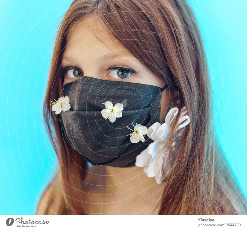 a girl in a black face mask decorated with flowers on a blue background beauty breathable care caucasian child cloth face covering colorful coronavirus covid