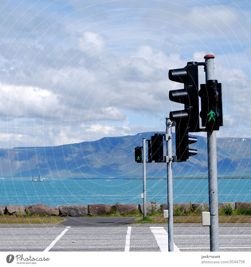 Open road for Icelanders Pedestrian lights Street Green Sky Clouds Ocean Landscape Nature Beautiful weather Summer green traffic light Environment Authentic