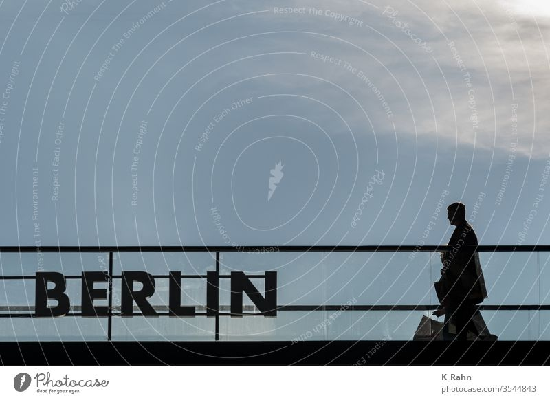 Man comes from shopping. Shopping Berlin stoop silhouette Back-light lettering Business Town Hotel Merchant Loft Window Sky German Clouds Room view Light