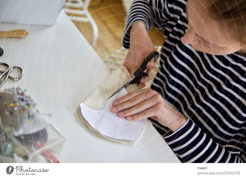 Brave little tailor | Young woman cuts a piece of fabric at her sewing table with the help of a pattern. Sewing Tailoring Handcrafts Cloth sewing accessories