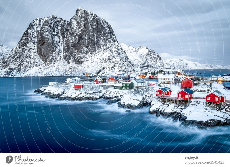 Hamnoy on the Lofoten with a view of the small red houses standing on snowy rocks at the blue hour Lofotes Norway Scandinavia Hamnøy Rorbuer Fishermans hut