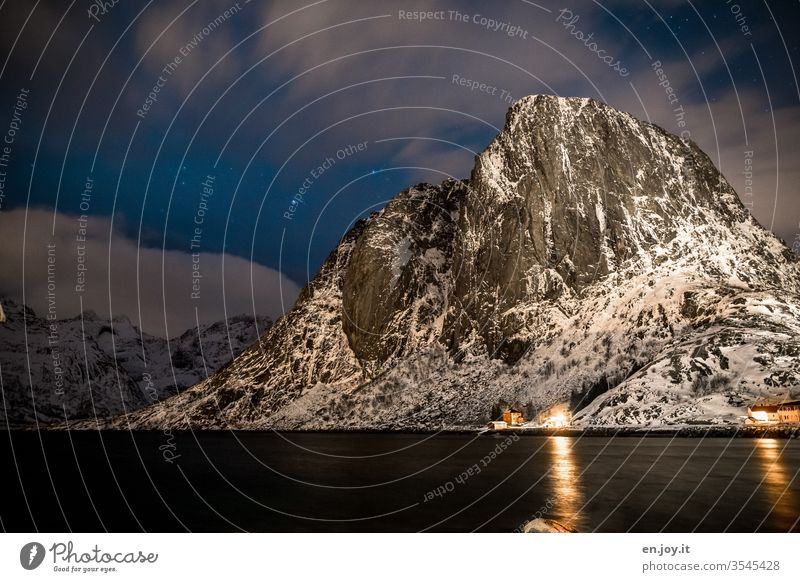 Mountain covered with snow at the blue hour mountain Snow Night Winter Fjord Reine Reinefjorden Hamnøy Starry sky Clouds Long exposure Vacation & Travel Norway
