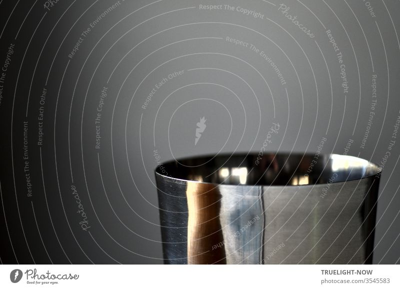 The upper part of a polished stainless steel cup reflects daylight reflections in front of a grey background and, in a distorted form, parts of its surroundings: an attempt at the Buddhist Heart Sutra
