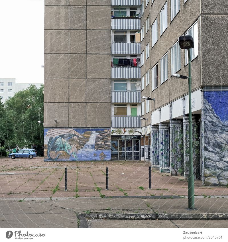 Panel building with courtyard, pavement, paintings and lantern Prefab construction Facade Apartment Building Berlin Lichtenberg Blue mural painting Lantern off