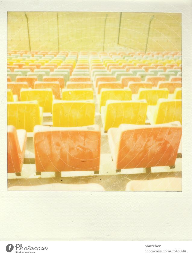 Polaroid. Colorful seats in a stadium. Sports facility, football. Turf Stadium variegated Orange Yellow green Lawn soccer Old Past Grating cordon Architecture