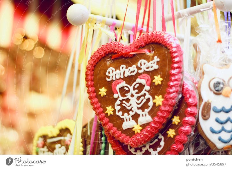 """Merry Christmas"" is written on a gingerbread heart. Christmas. Christmas fair. Kitsch. Lights. Gingerbread heart Christmas Fair stand candy Tradition"
